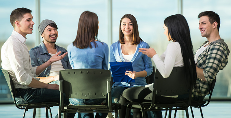 A focus group moderator conducts an in-person meet-up.